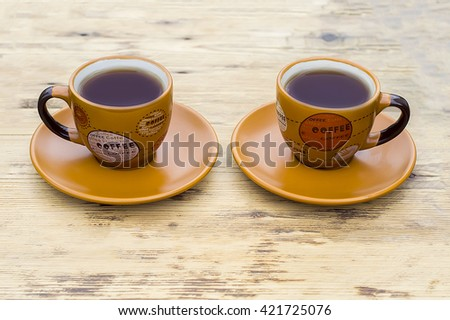 orange coffee Cup on a wooden table #421725076
