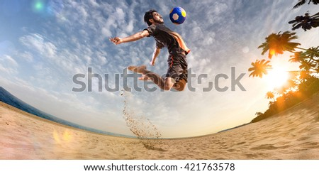 Beach soccer player in action. Sunny beach wide angle #421763578