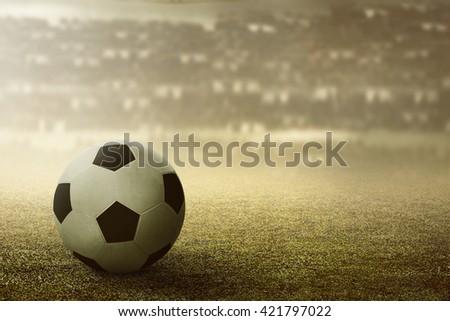 Football or soccer ball on football stadium grass