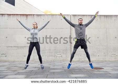 fitness, sport, people, exercising and lifestyle concept - happy man and woman doing jumping jack or star jump exercise outdoors Royalty-Free Stock Photo #421876885