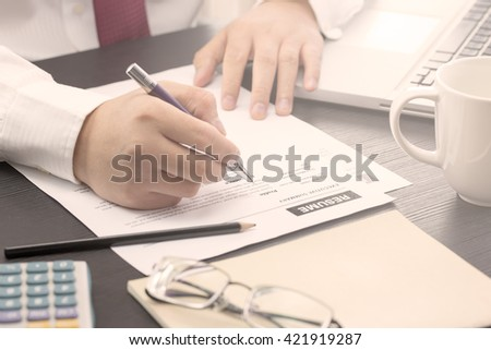 Business man review his resume on his desk, laptop computer, calculator, warm tone. #421919287