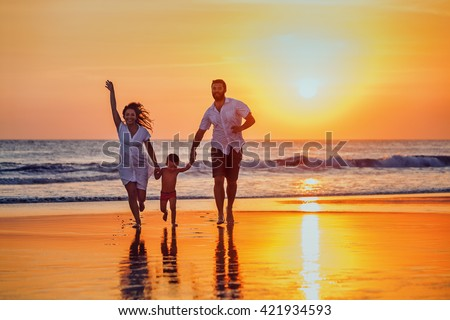 Happy family - father, mother, baby son hold hands and run with fun along sunset sea surf on black sand beach. Active parents and people outdoor activity on tropical summer vacations with children. #421934593