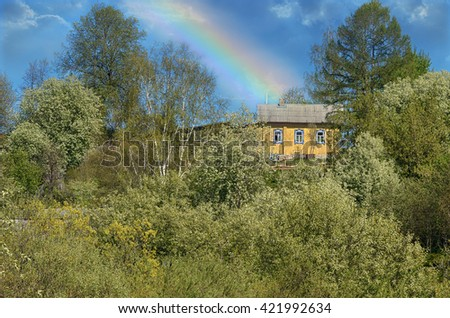 Rural spring landscape with rainbow after a storm, a house in the hills in the blossoming cherry tree. #421992634
