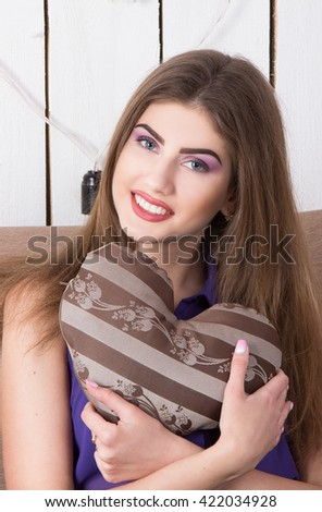 young beautiful woman with a pillow-heart in hands #422034928