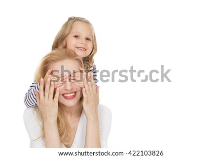 Her lovely mommy. Shot of cheerful little girl covering her mothers eyes with her hands looking to the camera smiling isolated on white. #422103826