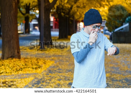 An Asian Man in a Polo T-shirt on Sidewalk of a Street with Yellow Ginkgo Trees in Autumn #422164501