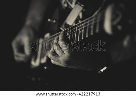 Closeup of man's hands playing guitar on the concert. Guitarist. Monochrome. Music concept
