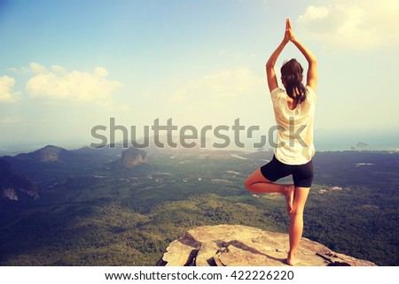 young fitness woman practice yoga at mountain peak cliff #422226220