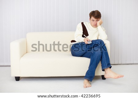 The young man misses sitting on a sofa at the TV #42236695