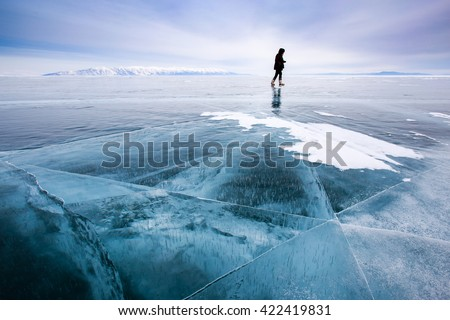 Girl photographer walking on cracked ice of a frozen lake Baikal Royalty-Free Stock Photo #422419831