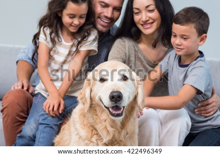 Family petting dog in living room #422496349