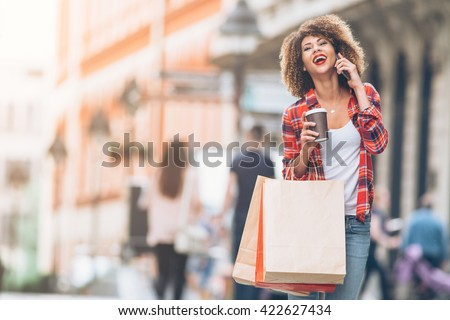 Young woman at the street with shopping bags talking on mobile phone  #422627434