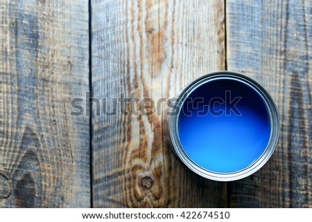 Bank with blue paint standing on wooden boards top view #422674510