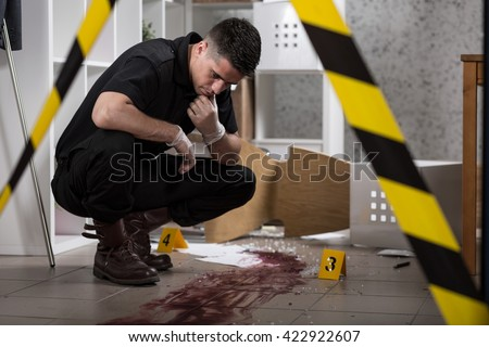 Young policeman collecting evidence standing behhind yellow crime scene tape #422922607