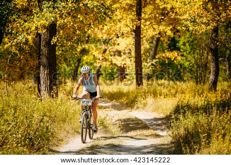 Gomel, Belarus - August 9, 2015: Young woman girl mountain Bike cyclist riding track at sunny day, healthy lifestyle active athlete doing sport. #423145222