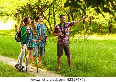 Group of young friends hiking trough forest on beautiful summer day.Man using binoculars. #423174748