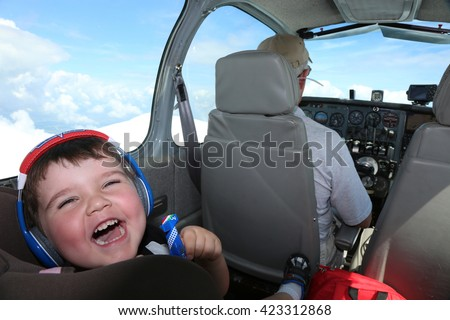 Young boy flying in small airplane with his grandpa with his headphones on laughing #423312868