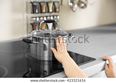 Little child playing with pan and electric stove in the kitchen #423321616