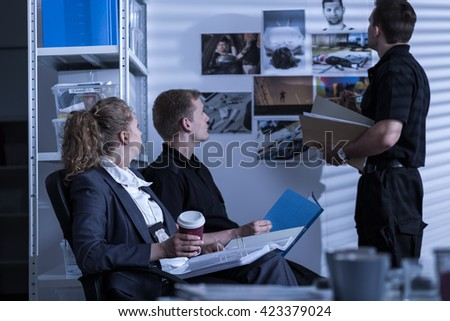 Shot of three police officers looking at pictures connected to a crime