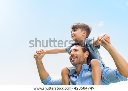 Father giving son ride on back in park. Portrait of happy father giving son piggyback ride on his shoulders and looking up. Cute boy with dad playing outdoor. Royalty-Free Stock Photo #423584749