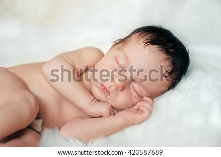 sleeping baby boy with milk on lips #423587689