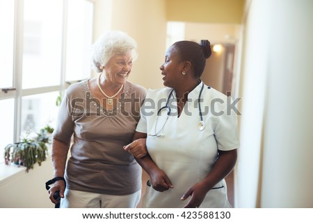 Senior woman walking in the nursing home supported by a caregiver. Nurse assisting senior woman.