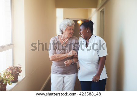 Portrait of happy female caregiver and senior woman walking together at home. Professional caregiver taking care of elderly woman. Royalty-Free Stock Photo #423588148