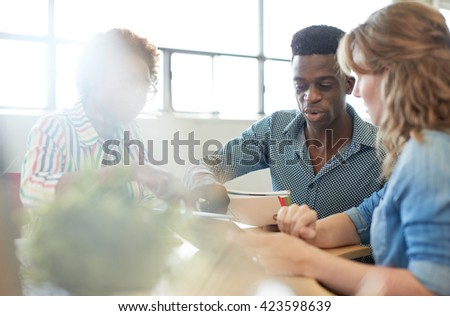 Unposed group of creative business people in an open concept office brainstorming their next project. #423598639