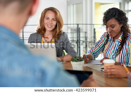 Multi ethnic group of succesful creative business people using a laptop during candid meeting #423599071