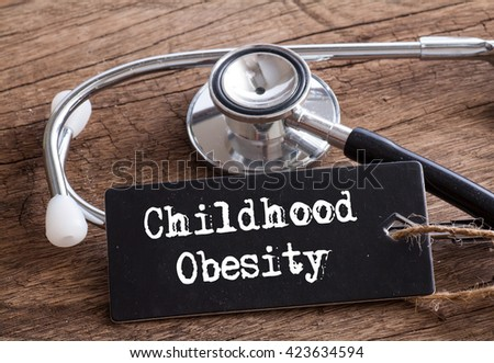 Stethoscope on wood with Childhood Obesity word as medical concept #423634594