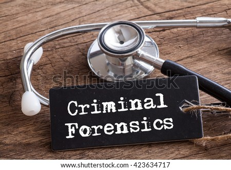 Stethoscope on wood with Criminal Forensics word as medical concept #423634717
