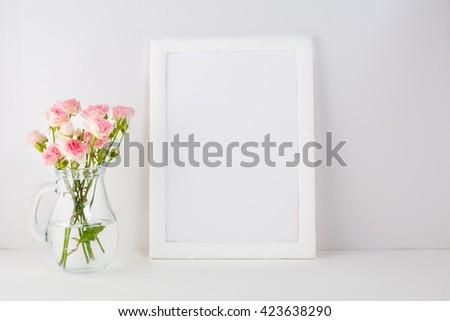 White frame mockup with pink roses. Frame mockup. White frame mockup. Poster product design styled mockup. Empty frame mockup.