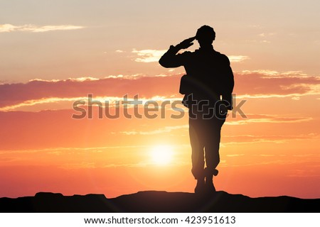 Silhouette Of A Soldier Saluting During Sunset Royalty-Free Stock Photo #423951613