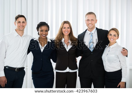 Group Of Happy Businesspeople Standing In Office #423967603