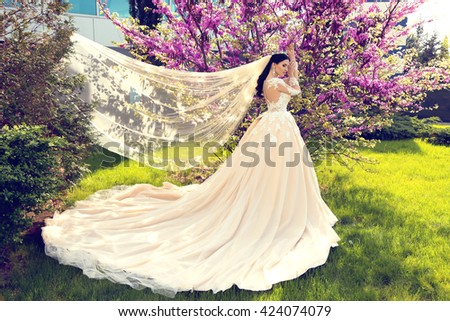 fashion outdoor photo of gorgeous woman in luxurious wedding dress posing at summer park #424074079