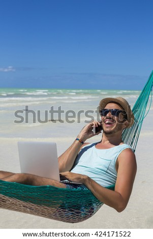 Man working with a laptop, on a hammock in the beach. Concept of digital nomad, remote worker, independent location entrepreneur. #424171522