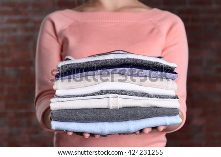 Woman hold clothes pile against brick wall background, close up #424231255