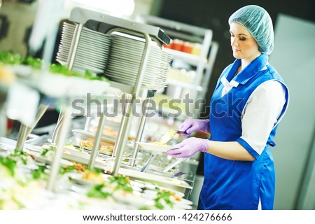 buffet female worker servicing food in cafeteria Royalty-Free Stock Photo #424276666