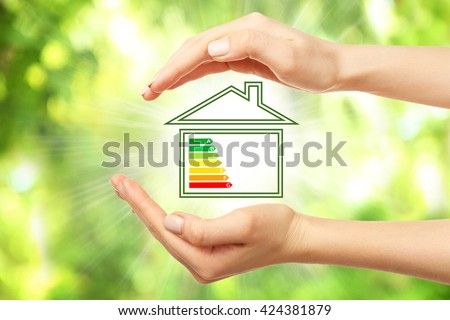 Female hands and house with energy efficiency scale image on natural background #424381879