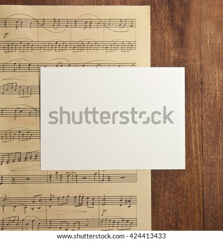 A photo of a blank white post card with copyspace, on a piece of aged sheet music (piano concert), on a dark wooden background texture, shot from above; an invitation template
