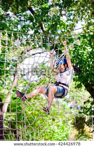 adventure climbing high wire park - people on course in mountain helmet and safety equipment #424426978