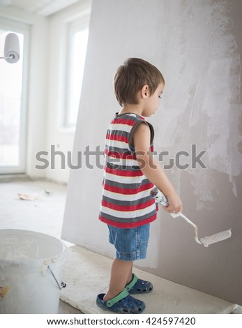 Little cute boy painting on a wall #424597420