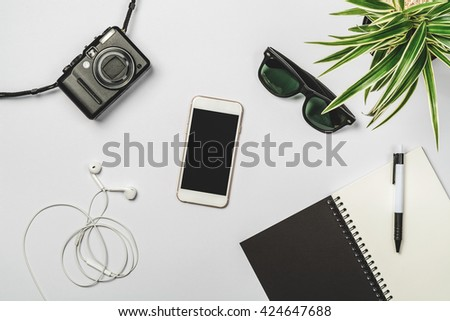 Flat lay photography with smart phone, earphone, notebook and pen, camera, sunglasses and garden tree