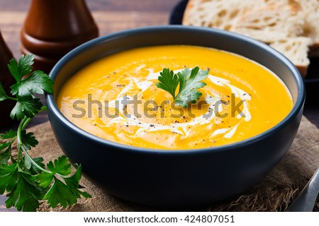 Pumpkin and carrot soup with cream and parsley on dark wooden background #424807051