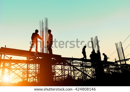 Silhouette construction industry engineer standing orders for worker  team to work safety on high ground over blurred background sunset pastel #424808146