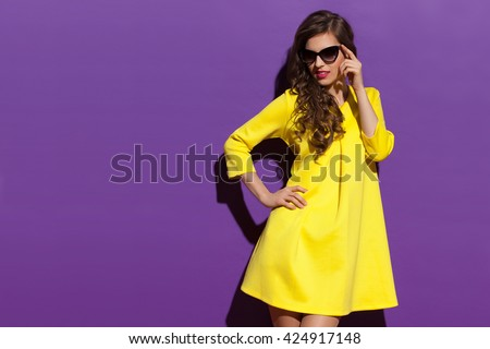 Beautiful elegance young woman in yellow mini dress and sunglasses holding hand on hip and looking away. Three quarter length studio shot on purple background. #424917148