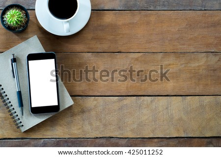 Office desk  table with blank screen smart phone, notebook pen and coffee cup .Top view with copy space.Office supplies and gadgets on desk table.Working desk table concept.Flat lay image.