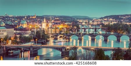 Prague, Czech Republic bridges panorama with historic Charles Bridge and Vltava river at night. Vintage #425168608