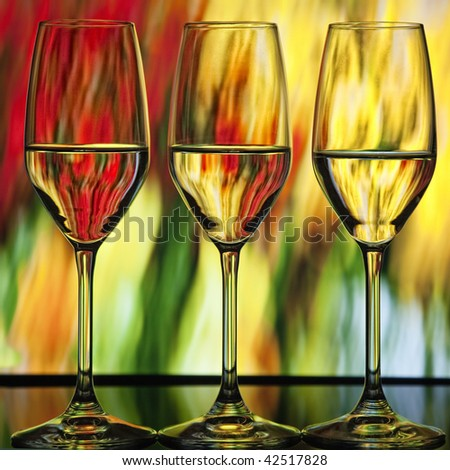 Three beautiful wine glasses with orange, green and yellow lighted background which looks like fire