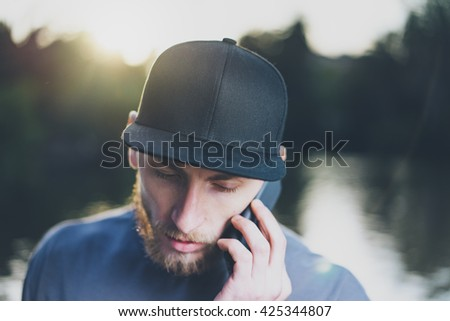Photo Bearded Young Man Wearing Black Blank Cap Using Modern Smartphone. Green City Park Lake Background and Sunset effect. Front view. Horizontal Mockup.